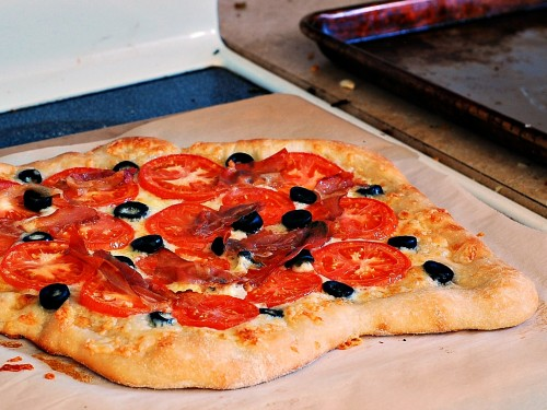 Pizza with Fontina, Tomatoes, Olives, and Prosciutto