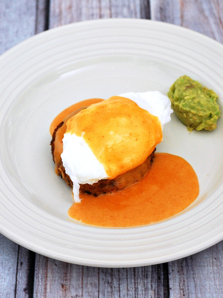 Celebrate #BrunchWeek with a fancy Eggs Benedict: a poached egg sits atop a crab cake, topped with tomato Hollandaise sauce, and served with avocado mash. theredheadbaker.com
