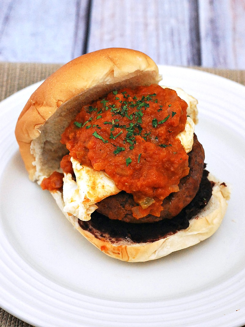 Add a kick to your brunch with huevos rancheros burgers! Spicy chorizo and beef burgers are topped with a poached egg and spicy huevos rancheros sauce. #BrunchWeek theredheadbaker.com