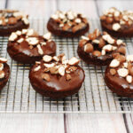 Chocolate malt baked donuts glazed in chocolate-malt glaze and topped with crushed malt candies are perfect for breakfast or dessert! TheRedheadBaker.com #TwelveLoaves