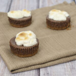 S'mores turn elegant in the form of mini chocolate cheesecakes with graham cracker crusts, topped with marshmallows toasted under the broiler. TheRedheadBaker.com #WhatsBaking