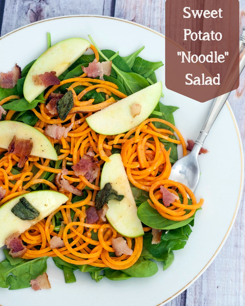 Sweet potato noodle salad swaps spiralized sweet potatos for pasta, served over spinach and apples with a delicious and tangy warm sage-brown-butter dressing. TheRedheadBaker.com