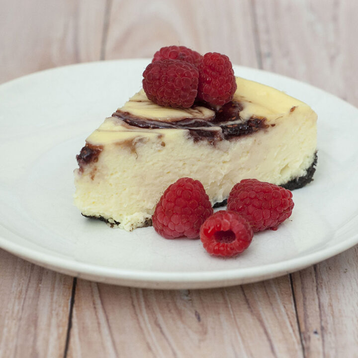 This incredibly rich and creamy white chocolate raspberry cheesecake has swirls of raspberry preserves — it looks difficult, but is to easy to make. #SundaySupper TheRedheadBaker.com