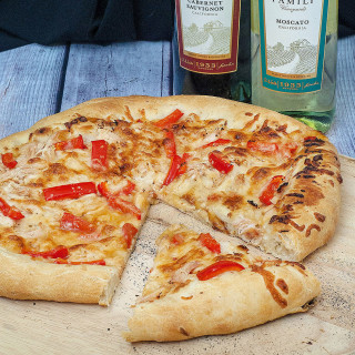 Make an exotic Thai chicken pizza for National Pizza month! Top homemade a pizza crust with sweet Thai sweet chili sauce, shredded chicken and bell peppers. #SundaySupper TheRedheadBaker.com