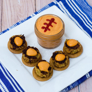 Bring some heat to your bowl game party with mini crab cakes served on RITZ® crackers, topped with spicy sriracha aioli. TheRedheadBaker.com #BowlTimeSnacks #ad