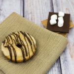 S'mores in donut form — are they for breakfast or dessert? Baked vanilla donuts are iced in marshmallow glazed, then dusted in graham cracker crumbs and a chocolate drizzle. TheRedheadBaker.com #WhatsBaking