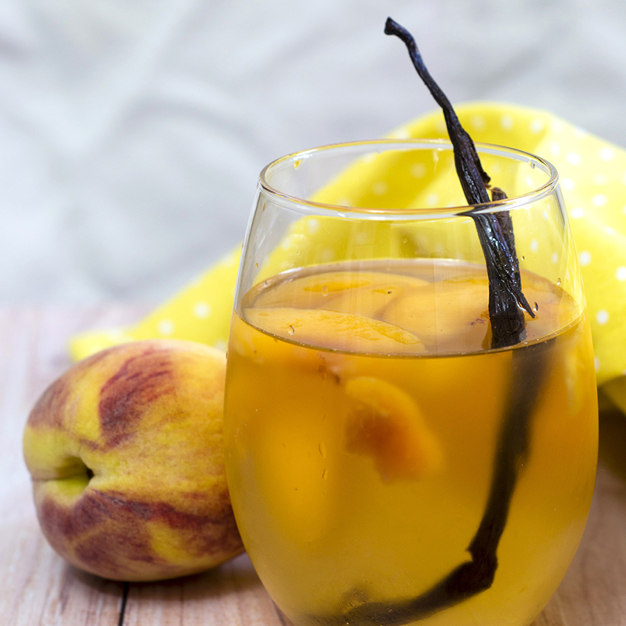 If you try one new cocktail this summer, make it this peach vanilla sangria. Crisp white wine is flavored with peaches, brandy and syrup infused with vanilla bean. #TheRedheadBaker