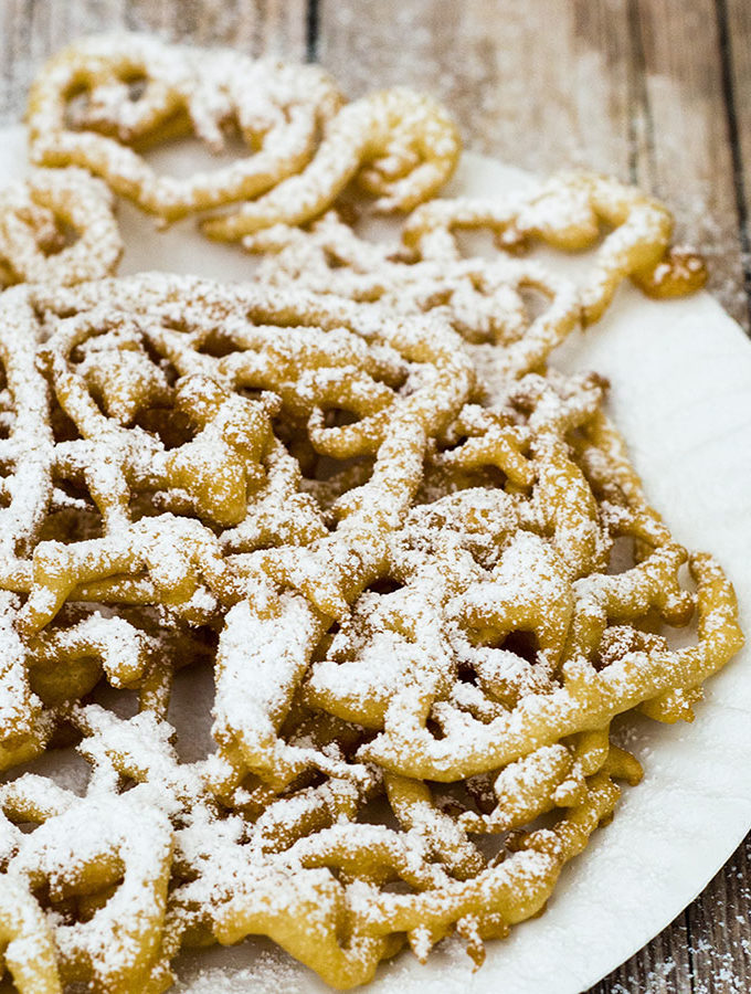 Boardwalk funnel cake takes me back to childhood vacations at a New Jersey beach. This warm deep-fried treat is dusted with powdered sugar and great for sharing! #SundaySupper TheRedheadBaker.com