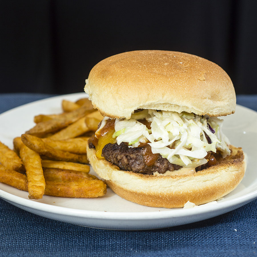 Carolina-style BBQ burgers are juicy beef patties topped with sharp cheddar cheese, tangy mustard- and vinegar-based BBQ sauce and coleslaw. #SundaySupper TheRedheadBaker.com