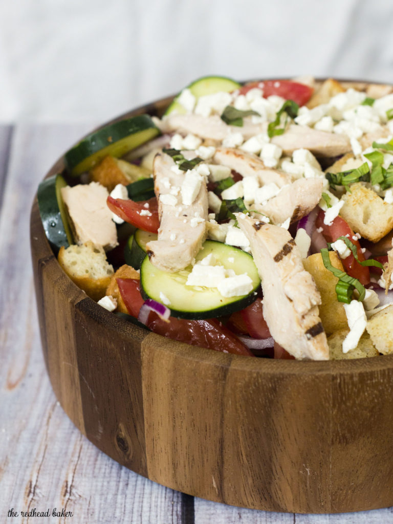 Greek Panzanella Salad is a perfect summer weeknight meal that combines tomato, red onion, cucumber, chicken and toasted bread with a homemade vinaigrette. TheRedheadBaker.com