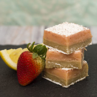 Strawberry lemon bars are a sweet twist on a tart classic bar cookie. These bars bring back memories of childhood summers drinking pink lemonade. #WhatsBaking TheRedheadBaker