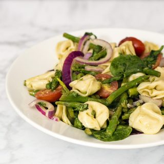 Tomato tortellini salad is my new favorite summer dinner! It combines lots of fresh, healthy vegetables, and comes together in under 30 minutes!