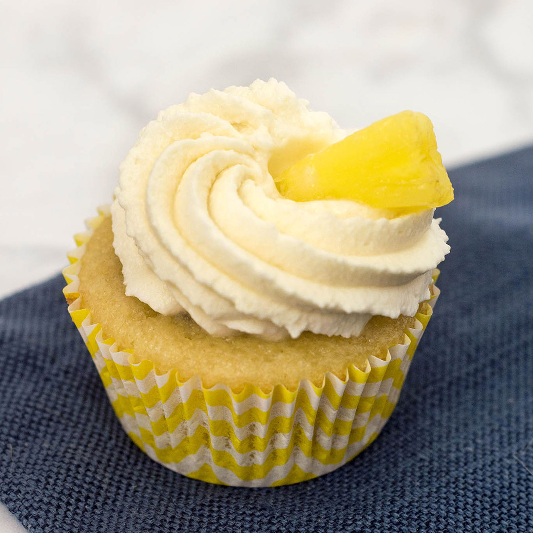 Pina colada cupcakes are soaked in rum syrup, filled with pineapple, and frosted with coconut whipped cream. A delicious summer treat! #SundaySupper