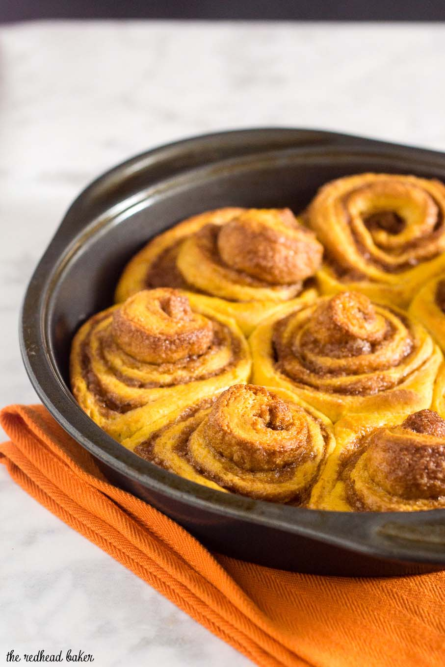 Pumpkin cinnamon rolls are a delicious way to start a fall morning! Sweet dough is flavored with pumpkin, rolled with a cinnamon filling, and topped with cream cheese drizzle. #PumpkinWeek
