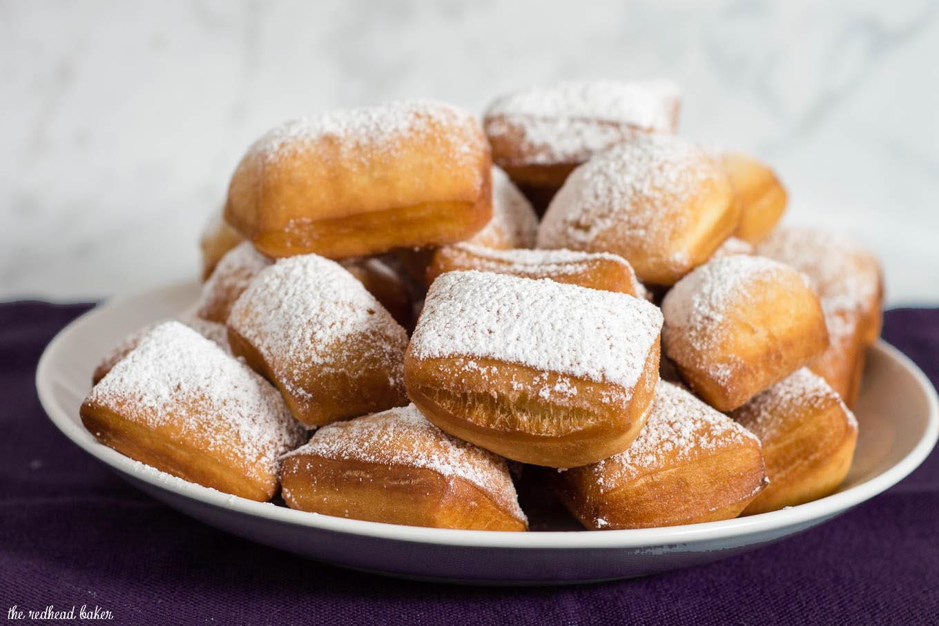 Mardi Gras means it's time for beignets! This is a classic New Orleans recipe, deep-fried then coated in powdered sugar, and served with raspberry jam.