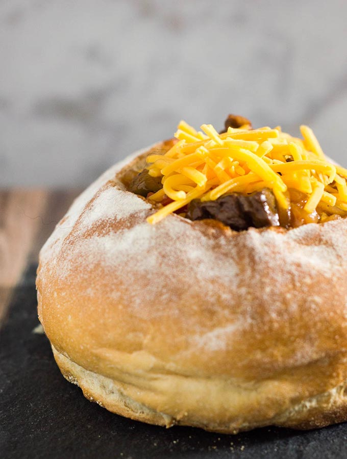 Philly cheesesteak chili has all the flavors of a traditional cheesesteak sandwich, topped with cheese and served in a hollowed-out bread bowl.