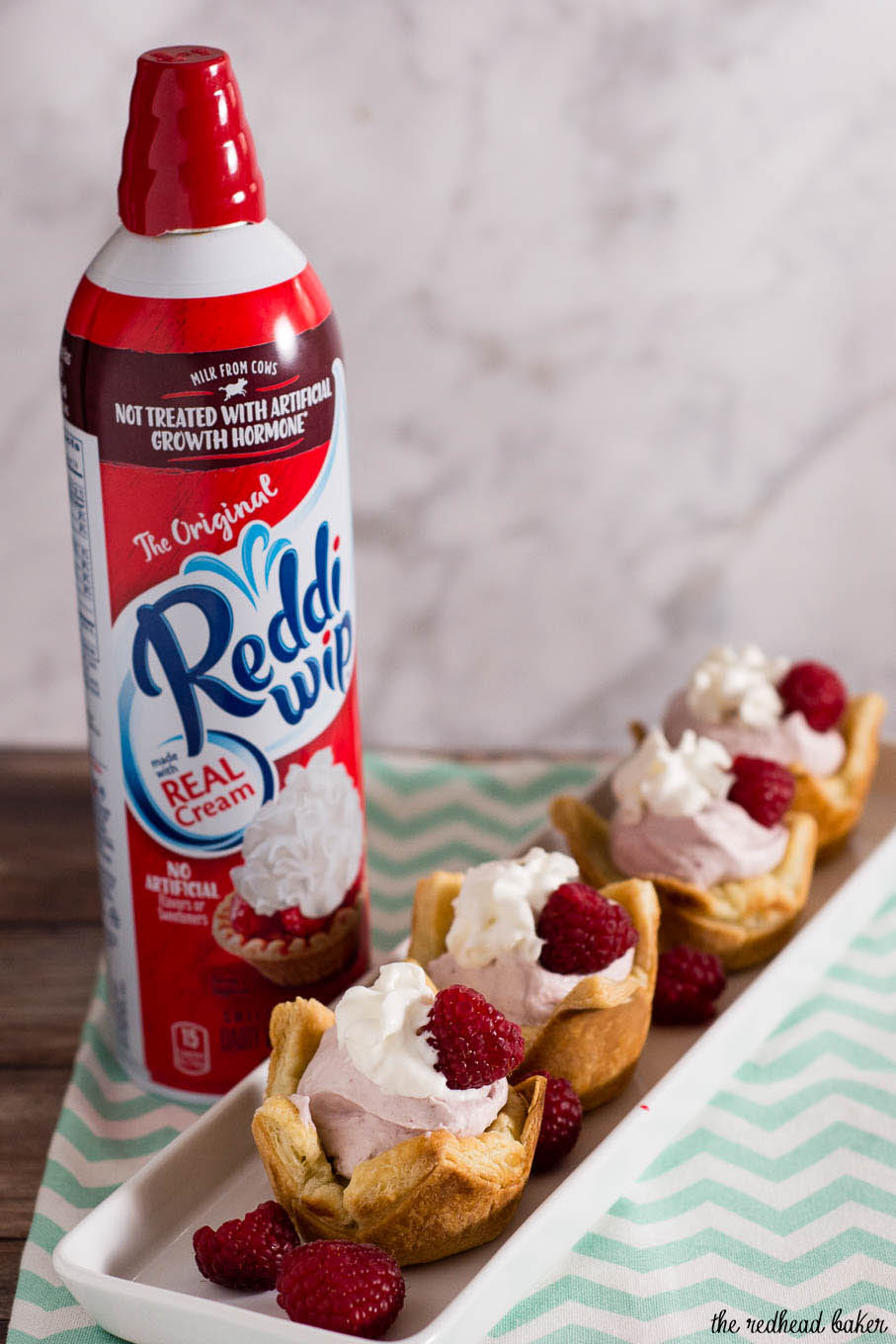 Mini raspberry mousse tartlets are full of spring flavor! Raspberry curd gives them a spring pink tint, and they are finished with a dollop of Reddi-wip®! #SpringReddi #ad