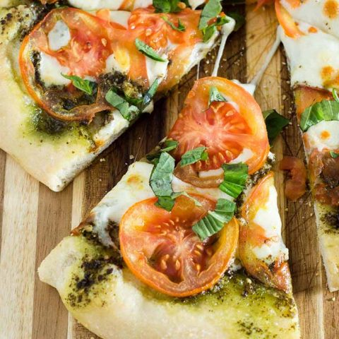 Caprese pizza is topped with pesto, thinly sliced tomatoes, and mozzarella cheese. Fresh basil and a balsamic glaze are added after baking.