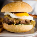 These French Bistro Burgers are full of over-the-top flavor: an herb aioli, smoked gouda cheese, bacon and a sunnyside up egg. Serve with rosemary fries or a frisee salad. #BurgerMonth #GirlCarnivore