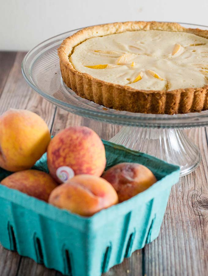 This peach custard tart has a crumbly cookie crust and a creamy custard filling loaded with tender peach slices. It's a delicious end to any meal! #BrunchWeek