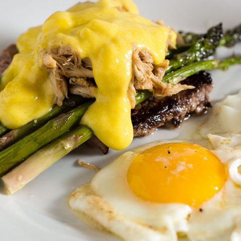 The classic brunch staple of steak and eggs gets fancy! The steak is served Oscar-style with asparagus, crab meat and Hollandaise sauce, with two sunny side-up eggs. #BrunchWeek