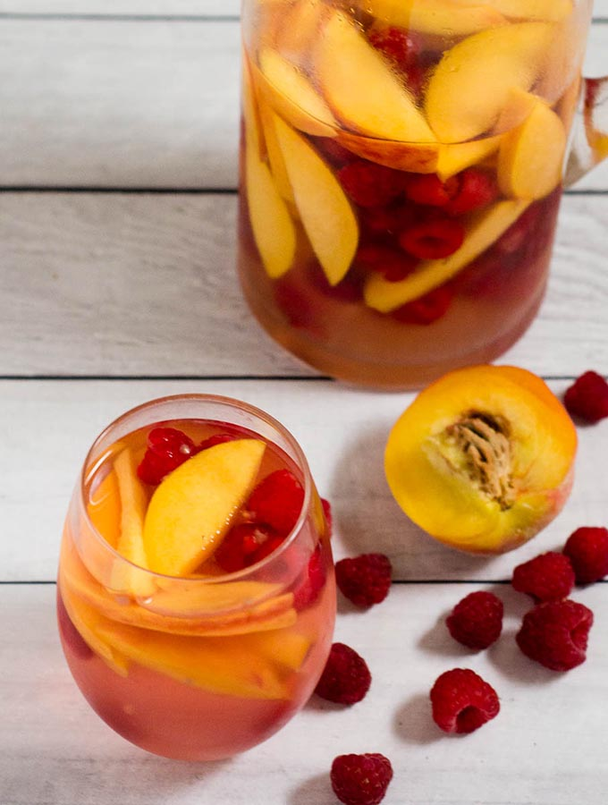 Fresh, sweet summer fruit balances dry white wine in this raspberry peach sangria. It's the perfect summer cocktail for any summer occasion.