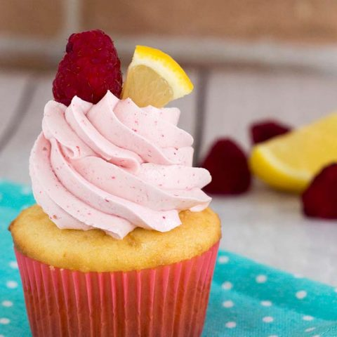 Raspberry lemon cupcakes are a delicious summer dessert. These fluffy cupcakes are filled with tart lemon curd and topped with silky buttercream flavored with raspberry puree. #FarmersMarketWeek