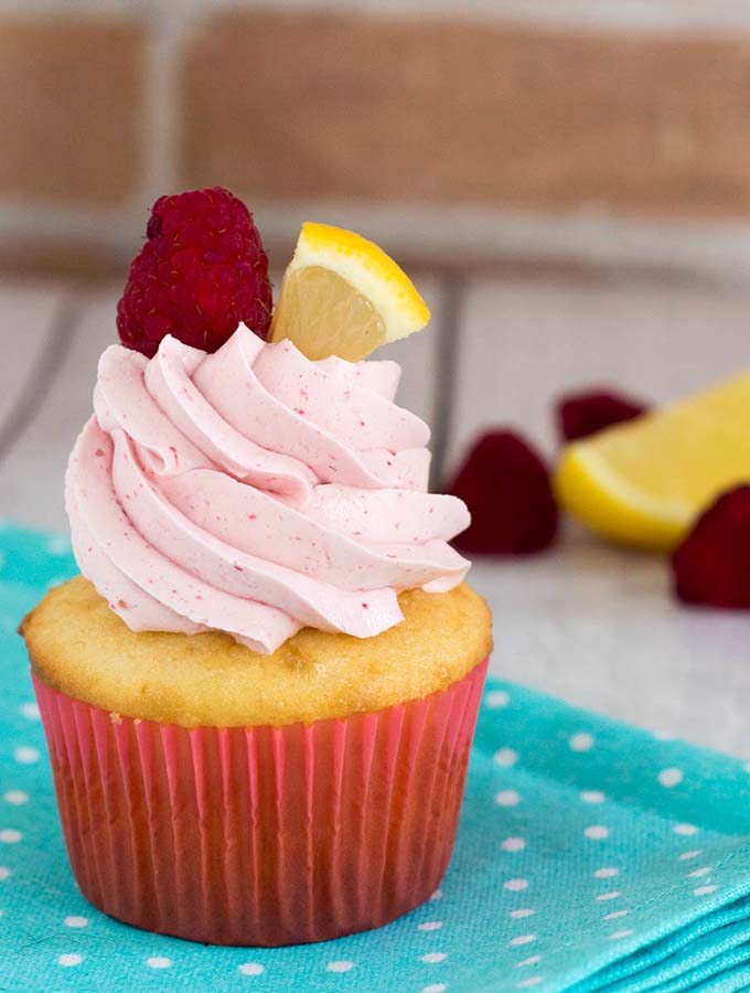 Raspberry lemon cupcakes are a delicious summer dessert. These fluffy cupcakes are filled with tart lemon curd and topped with silky buttercream flavored with raspberry puree.#FarmersMarketWeek