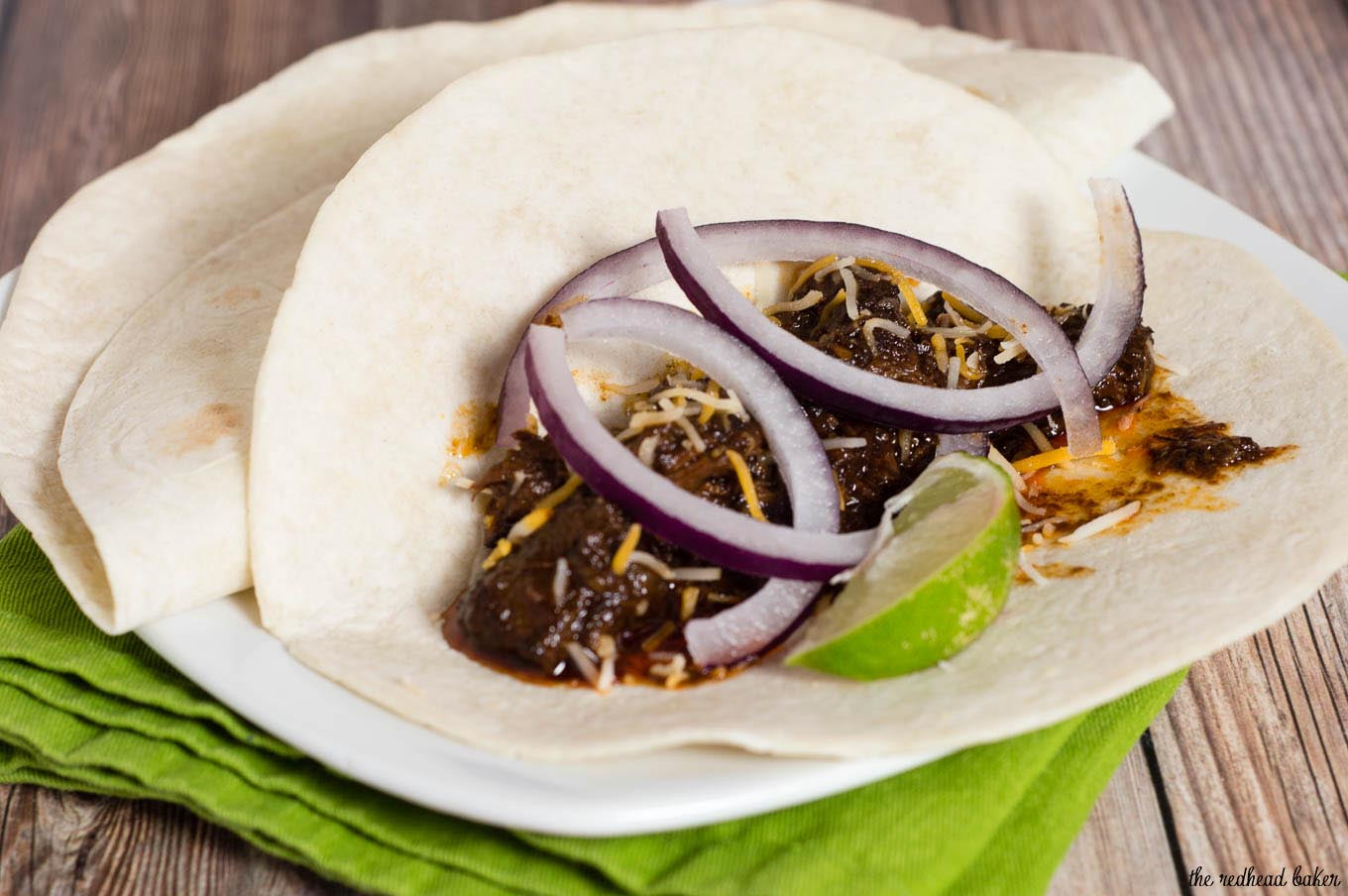 Authentic barbacoa beef tacos are piled with shredded beef cooked low and slow in chili-pepper spiced sauce, and topped with cilantro, salsa and lime wedges.