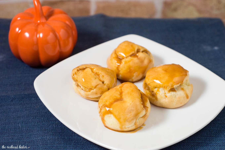 Pumpkin cream puffs are filled with creamy pumpkin custard and dunked in caramel glaze.You've never had a pumpkin dessert like this before!#PumpkinWeek