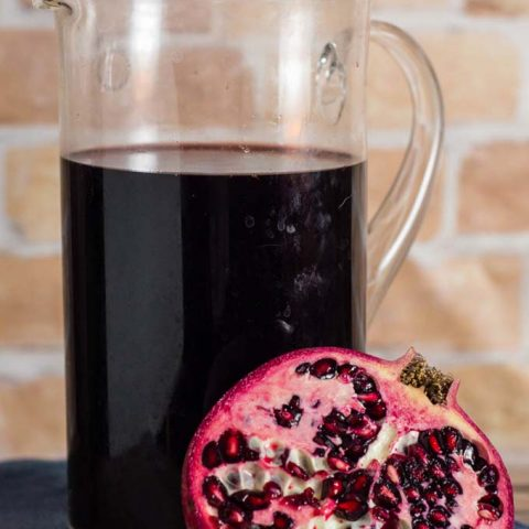 Spiced pomegranate red wine punch is a delicious cocktail for holidays and average days alike. Serve it warm or cold, garnished with a twist of orange rind.