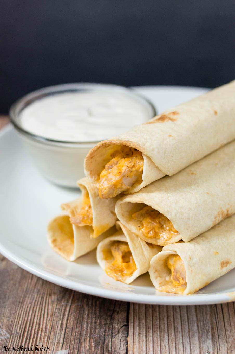 A plate of baked buffalo chicken taquitos and ranch dipping sauce.
