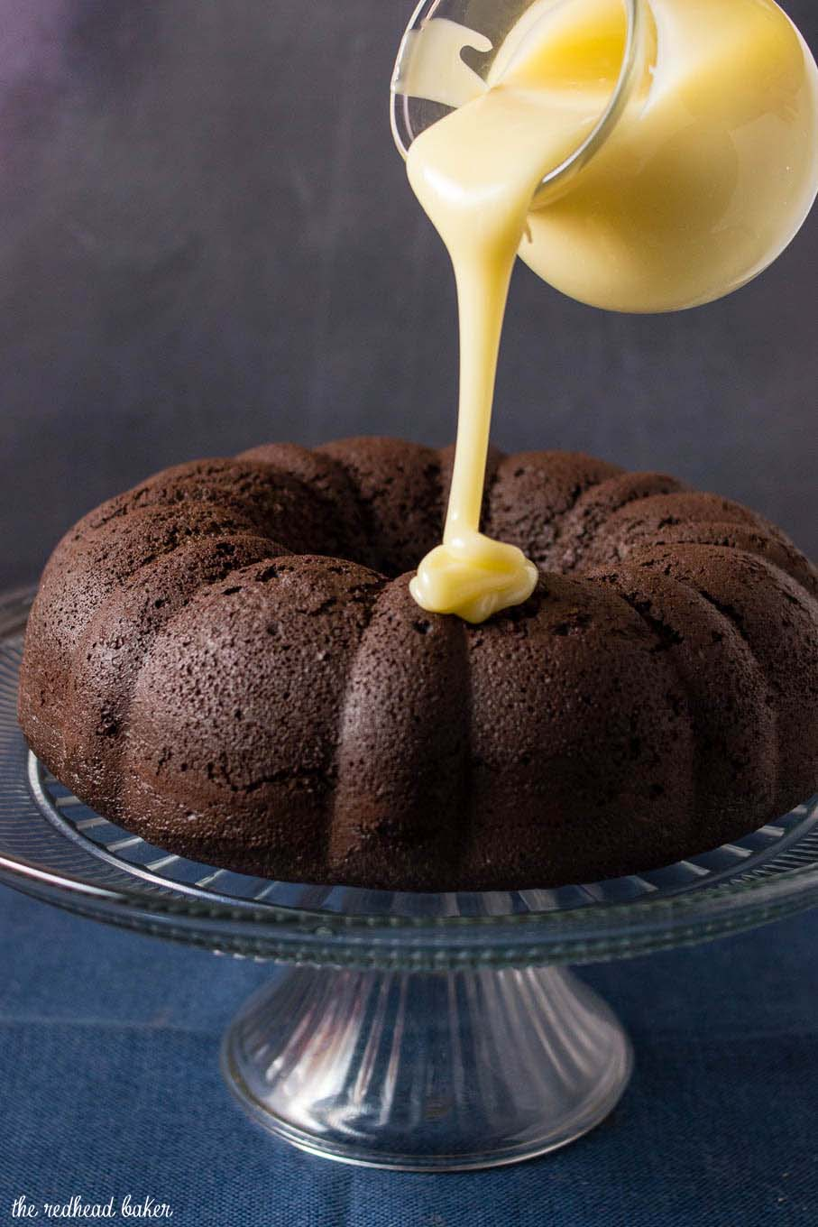 A shot of white chocolate icing being poured onto fudgy chocolate bundt cake.
