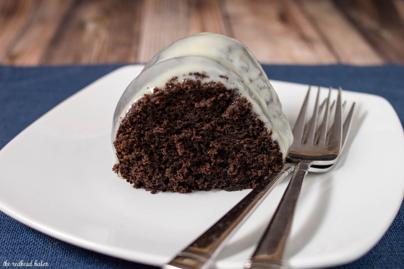 A slice of fudgy chocolate bundt cake on a white plate.
