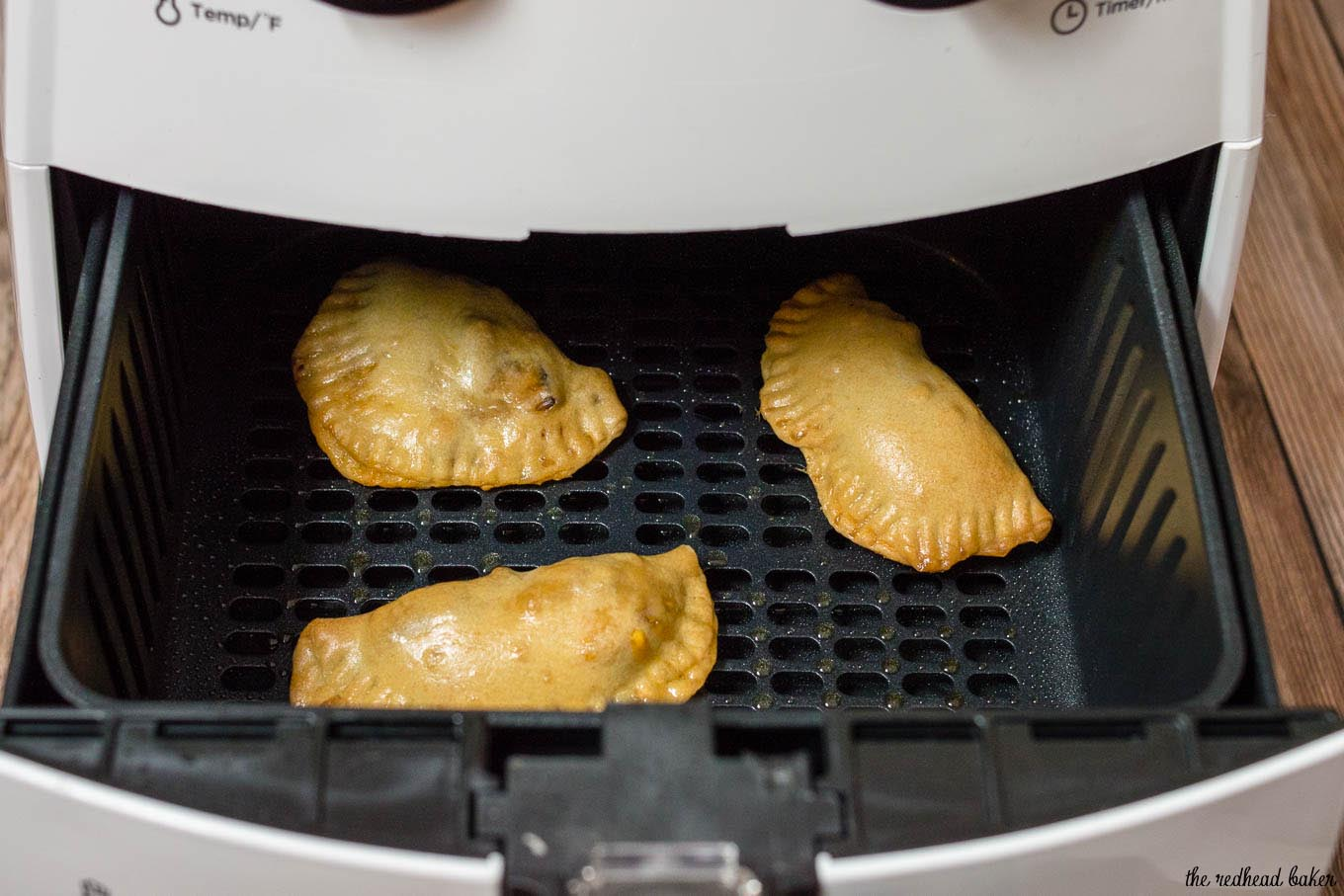 Cooked Philly cheesesteak empanadas in the basket of the air frye.r