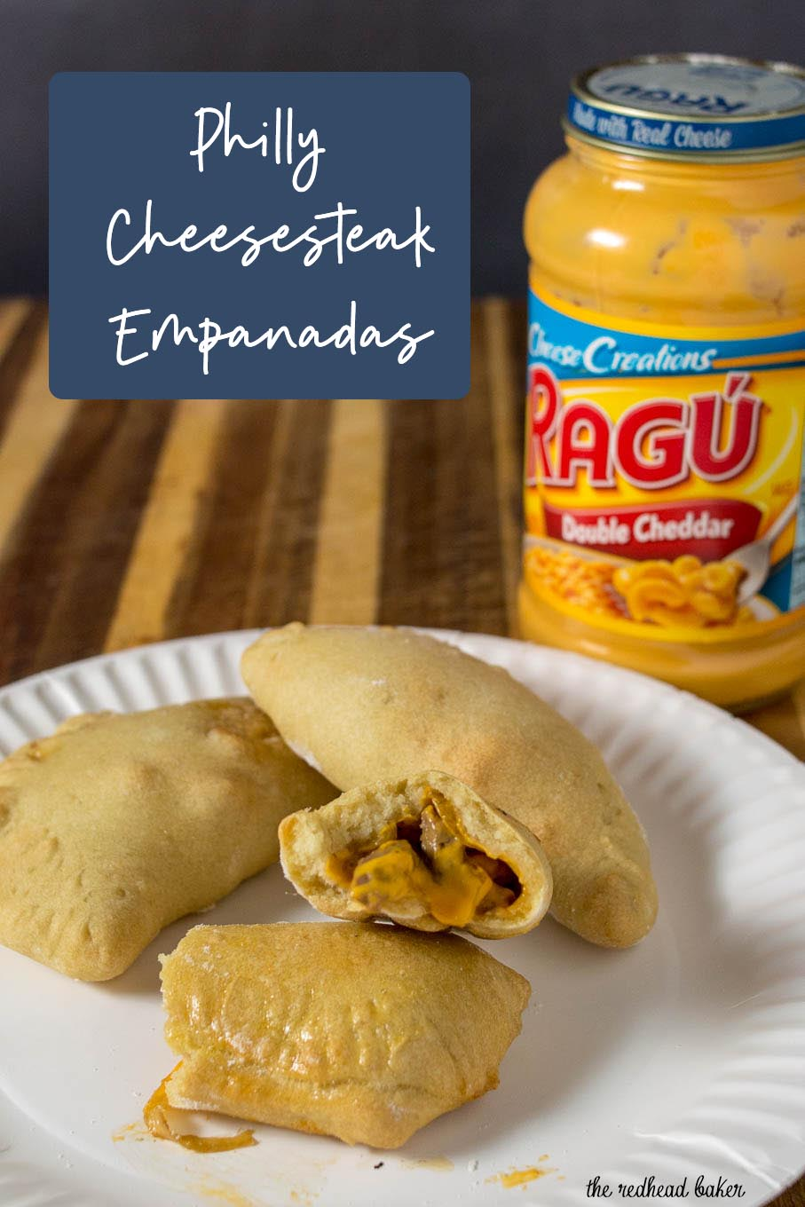 A plate of Philly cheesesteak empanadas with a jar of Ragu Double Cheddar Sauce.