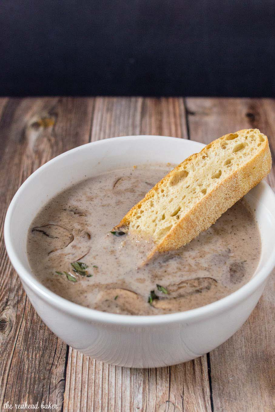 A piece of ciabatta bread being dipped in a bowl of port wine cream of mushroom soup