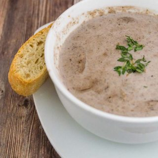 A bowl of port wine cream of mushroom soup with a stick of ciabatta bread on the side