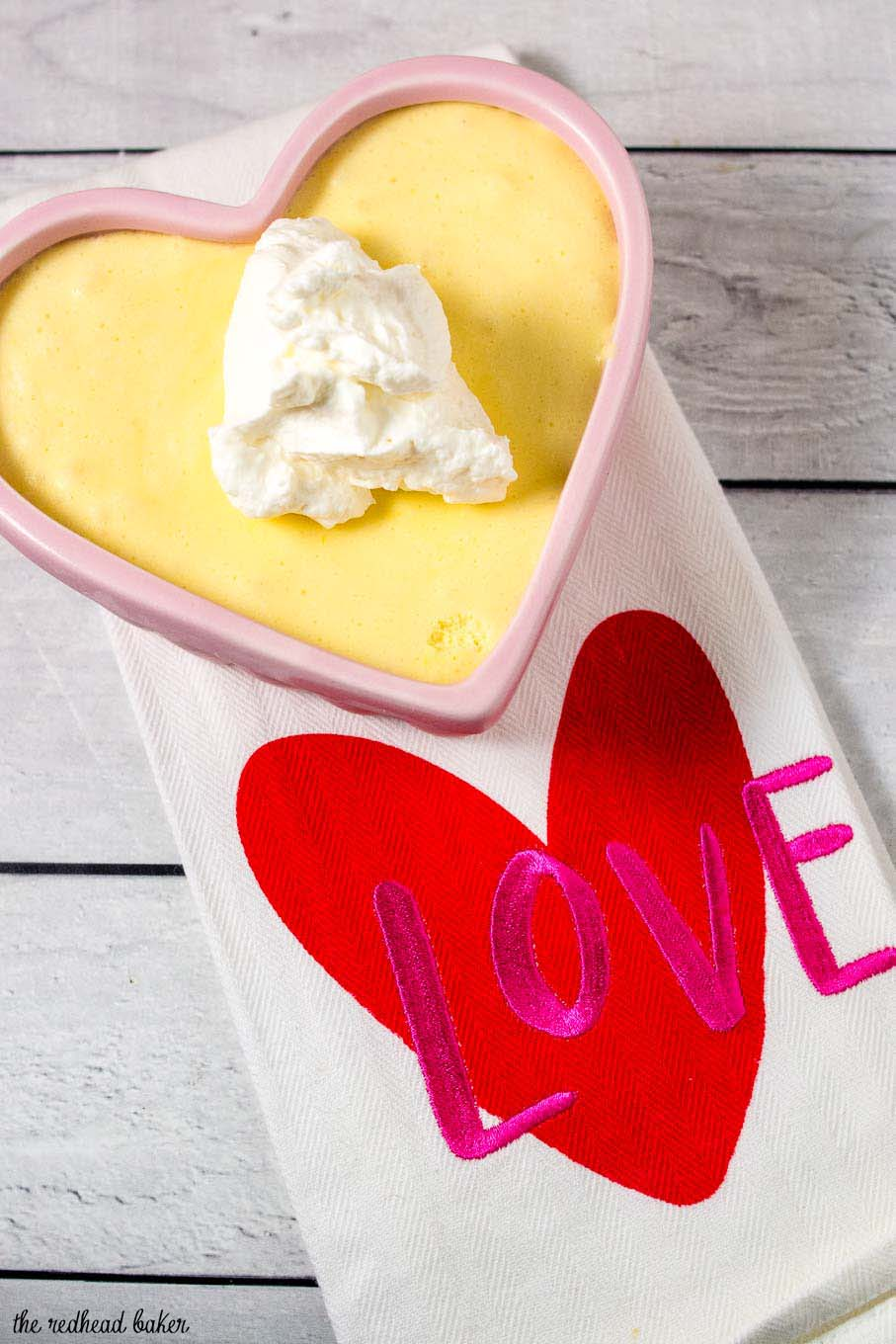 """A ramekin of white chocolate frozen mousse on a white tea towel with the word """"LOVE"""" embroidered on it."""