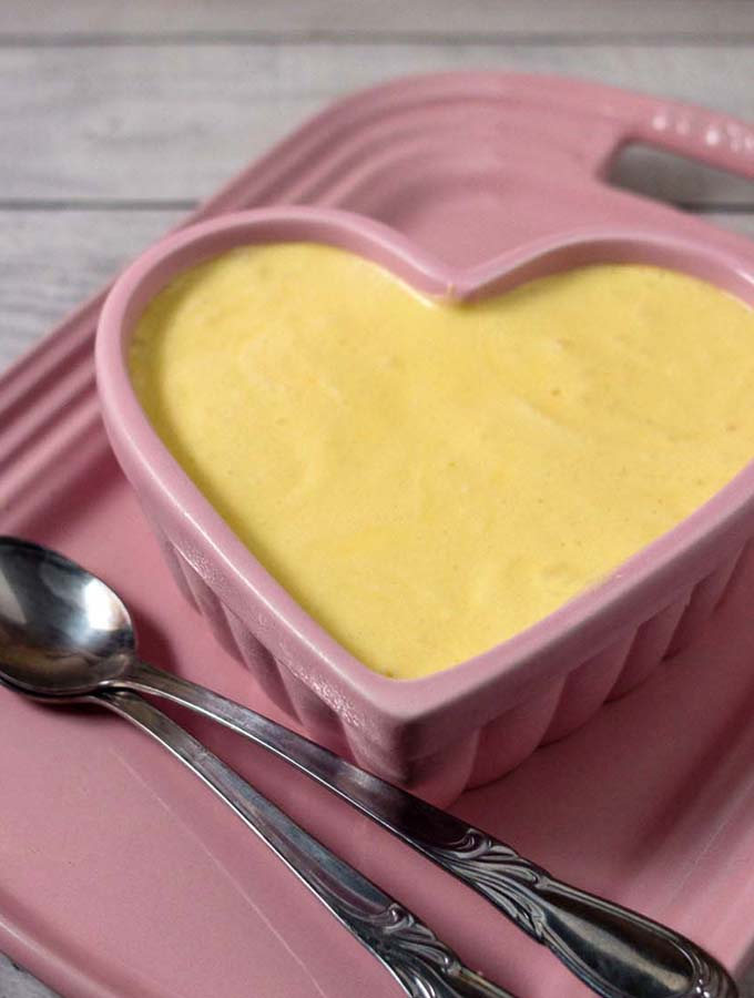 A ramekin of white chocolate frozen mousse on a pink serving tray.