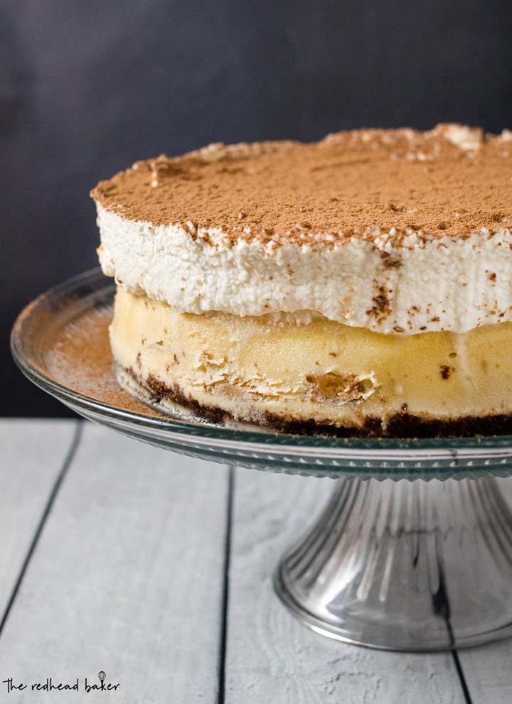 Tiramisu cheesecake on a glass cake stand.