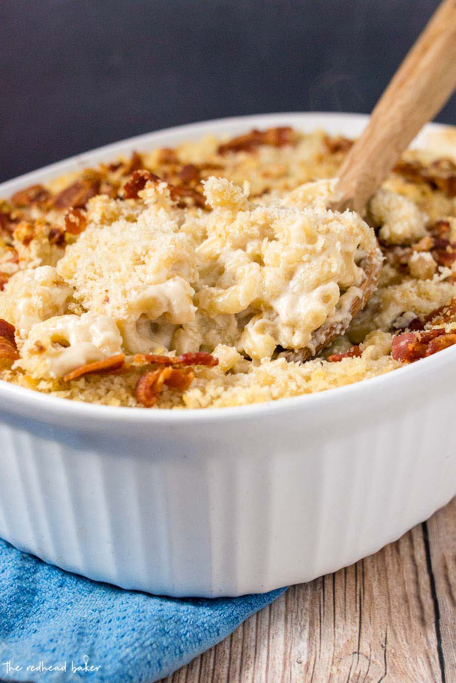 A wooden spoon digging into a casserole dish of Irish mac and cheese.