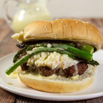 Surf-n-turf meets backyard cookout in these Oscar-Style Burgers. Hamburger patties are topped with crab meat, tender-crisp asparagus and rich Bearnaise sauce. #BurgerMonth