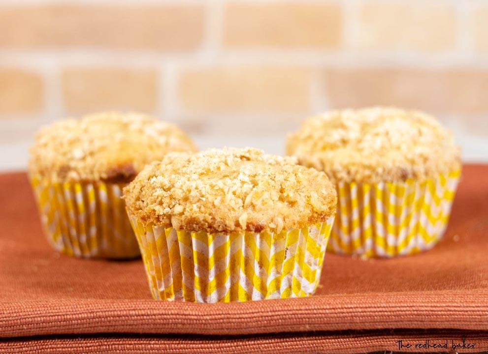 Three bakery-style peach crumb muffins