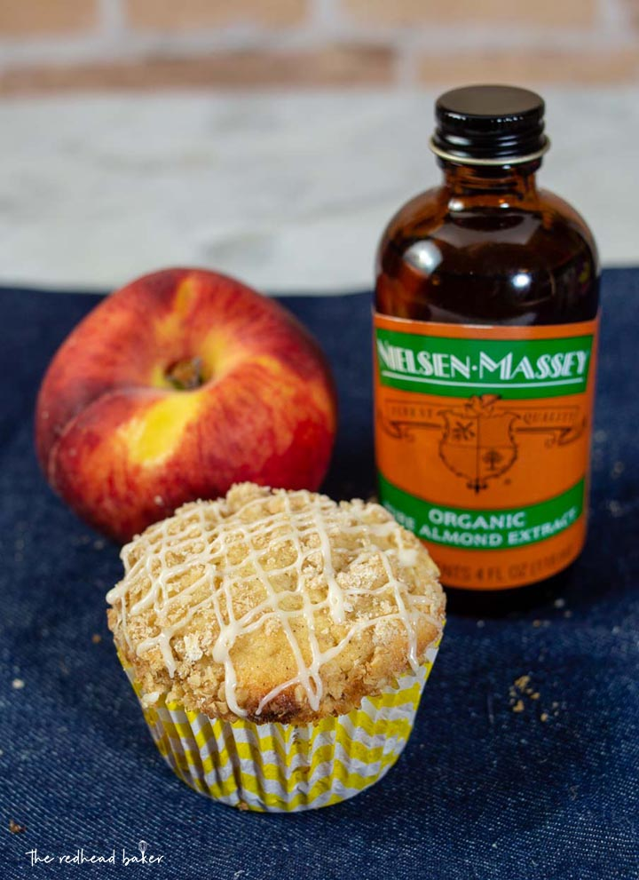 A bakery-style peach crumb muffin, a fresh peach, and a bottle of Nielsen-Massey Organic Almond Extract.