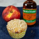 A bakery-style peach crumb muffin, a fresh peach, and a bottle of Nielsen-Massey Organic Almond Extract