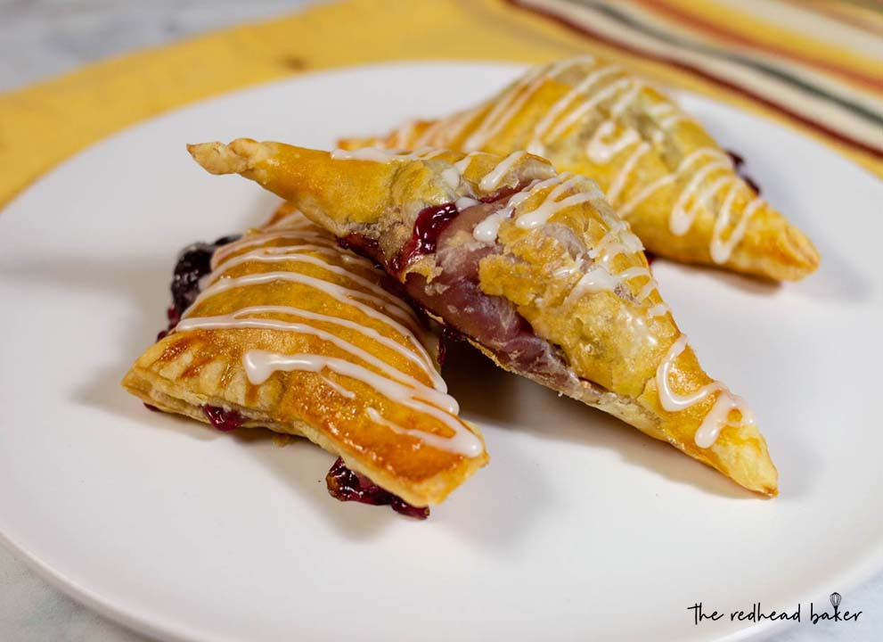 Three cherry turnovers on a plate.