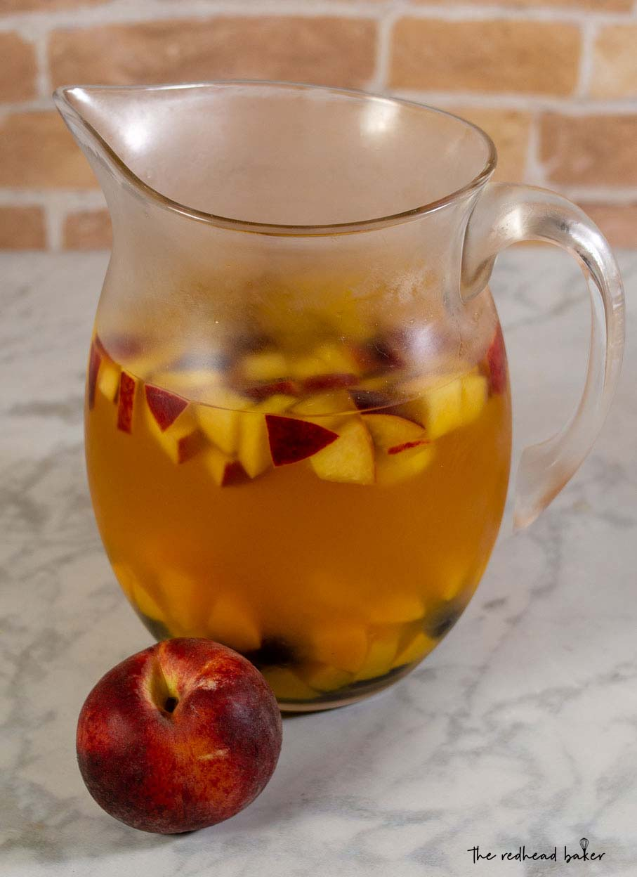 A pitcher of sparkling peach blackberry sangria with a whole fresh peach.