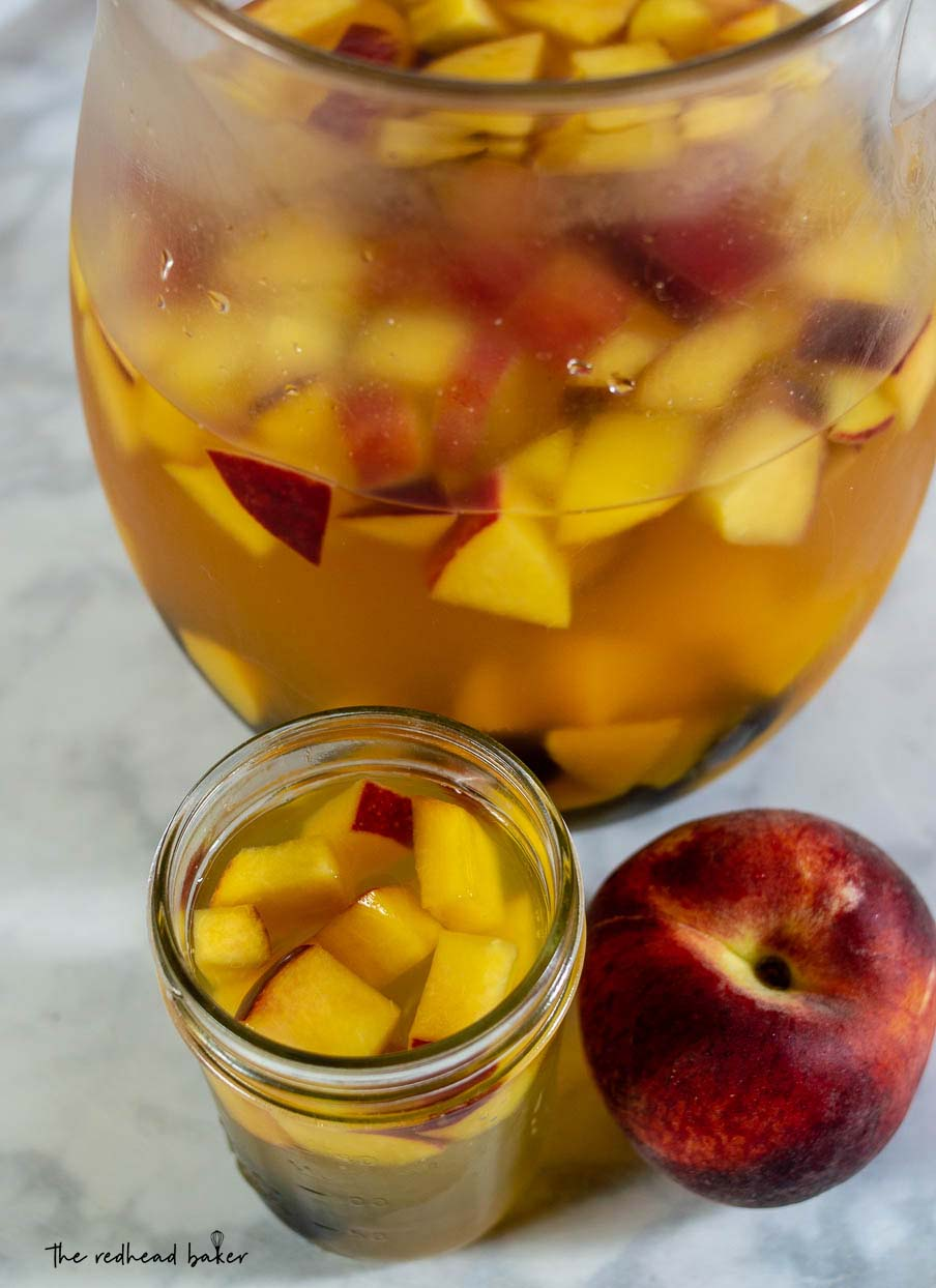 An overhead shot of a glass of sparkling blackberry peach sangria, the pitcher and a fresh peach.