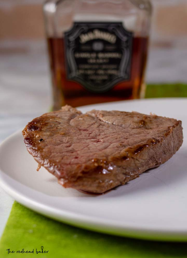A piece of pan-seared steak in front of a bottle of whiskey.